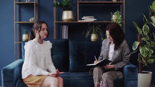 young doctor talks to young patient girl and explains how to deal with the disease