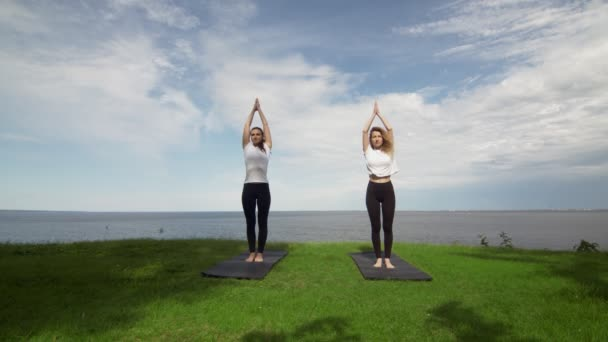 Two young women practice yoga on beach by the sea or ocea. Training Standing Hand to Toe pose and then Standing Half Lotus