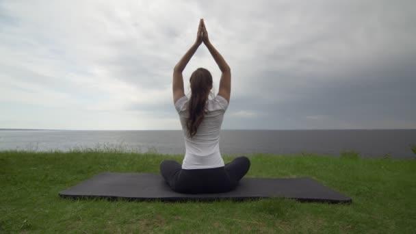 Junge, fitte Frauen praktizieren Yoga an der Küste in der Nähe des Sees oder Meeres. Frau sitzt in Lotus-Pose und meditiert
