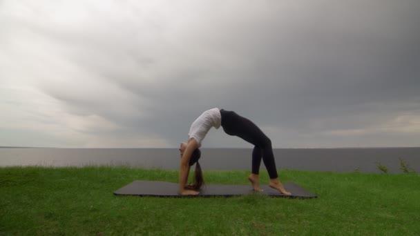 Young fit woman practice yoga on coast near the lake or sea. Woman doing Wheel Urdhva Dhanurasana pose