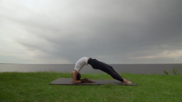 Fiatal nő gyakorolja jóga a parton, közel a tó vagy a tenger. Nő csinál fordított személyzet Dvi Pada Viparita Dandasana pózol