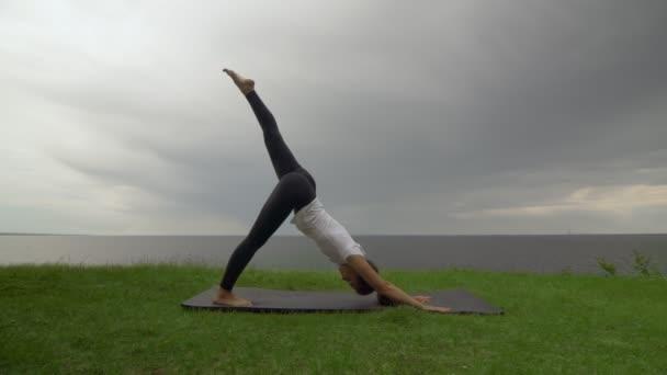 Mladá fit žena cvičí jógu na pobřeží u jezera nebo u moře. Žena dělá třínohý dolů-čelí pes pak bojovník I Poses