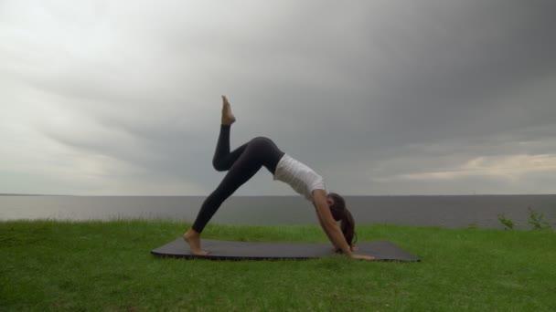 Mladá fit žena cvičí jógu na pobřeží u jezera nebo u moře. Žena dělá třínohý pes dolů a pak bojovník jeden a dva pózy