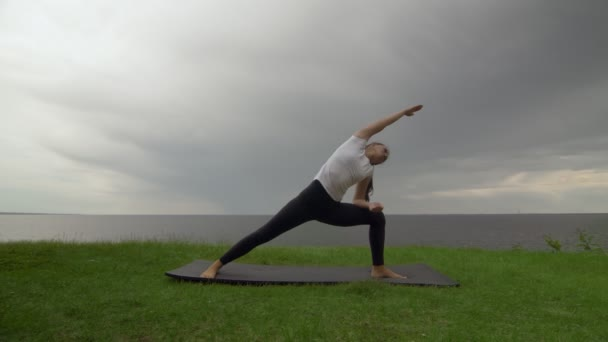 Young fit woman practice yoga on coast near the lake or sea. Woman doing Warrior two then Upward-Facing Dog Poses