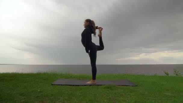 Mladá fit žena cvičí jógu na pobřeží u jezera nebo u moře. Žena tančí Lord of the Dance Natarajasana Pose