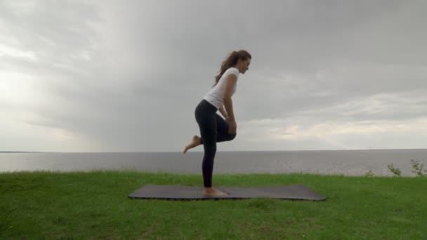 Junge, fitte Frauen praktizieren Yoga an der Küste in der Nähe des Sees oder Meeres. Frau balanciert im Stehen und beugt sich dann nach vorne