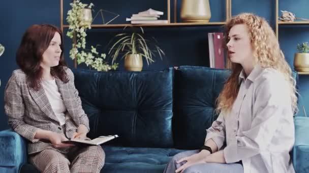 Mladá žena na konzultaci s psychologem. Pacient sedí na gauči a mluví o duševních problémech. Odborná pomoc, podpora psychologa, psychiatra, terapeuta.