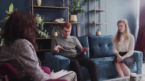 Mladý pár na poradně s psychoterapeutem. Back Pohled terapeuta psychologa dává rady manželskému páru. Rozzlobený muž mluví o její ženě.