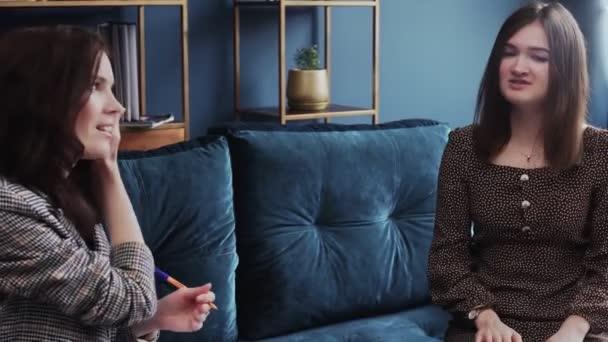 Atraktivní mladá žena sedí na pohodlném gauči, setkání psycholog.