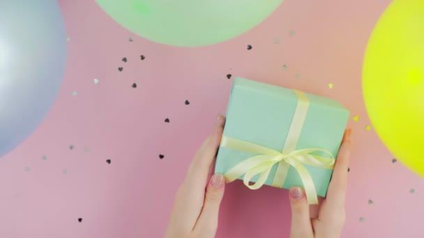 Žena putts vánoční dárek box zabalený v zeleném papíru na růžovém stole