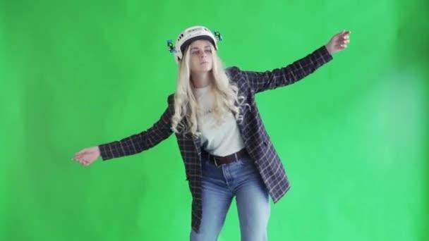 Blondýny žena v helmě bláznivé tance na zelené obrazovce