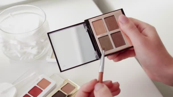 A palette with eye shadows and a makeup brush. Close up of woman make up cosmetics palette with differents powder colors