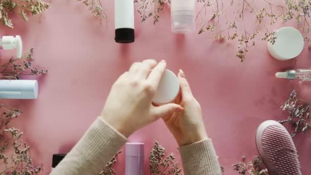 A nő testápolót tesz a kezére. Szépség téma lapos feküdt kreatív elrendezés felett pro környezet.