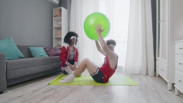 Lustiges Paar im Retro-Stil aus kaukasischen Männern und Afrofrauen bei der Arbeit zu Hause. Lustiger Mann macht Bauchmuskelübungen knirscht mit Fitnessball zu Hause mit Frau, Fitness Humor.