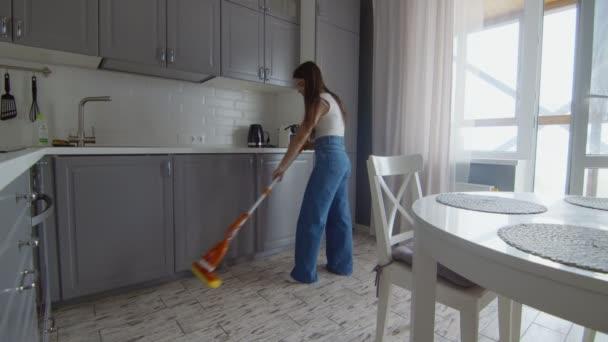 Mladá krásná žena čistí podlahu s mop v kuchyni
