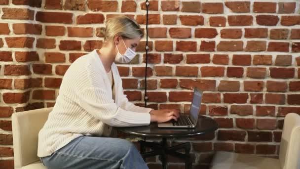 Fiatal üzletasszony védő maszk dolgozik notebook kávézóban