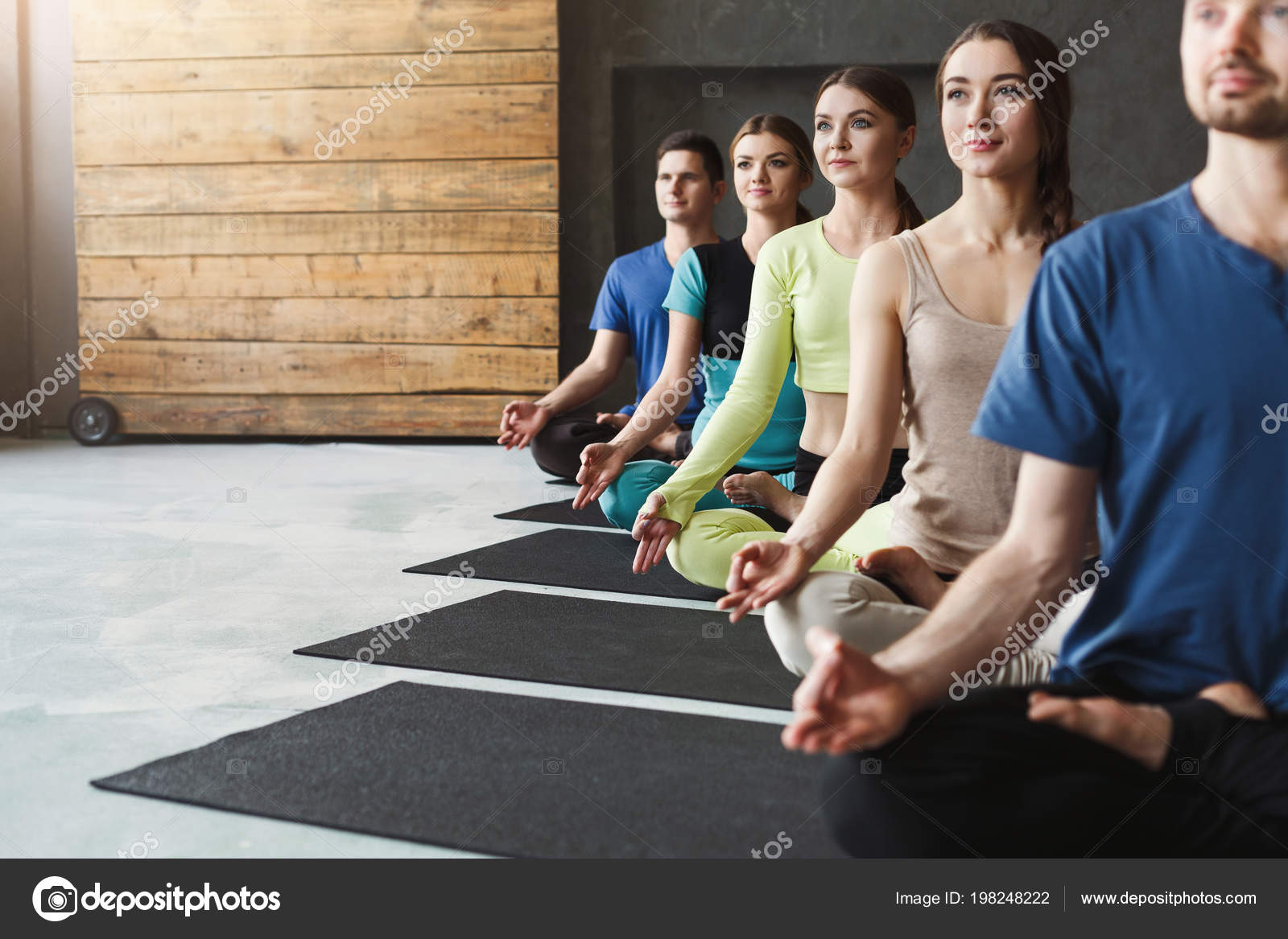 Young Women And Men In Yoga Class Relax Meditation Pose Stock Photo