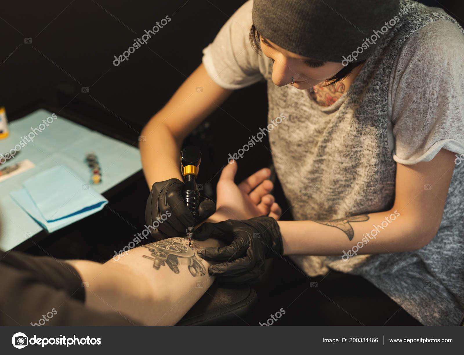 Concentrato il tatuatore donna fare il tatuaggio con macchina tatuaggio sul  braccio maschio 8c6b85ad9d2f