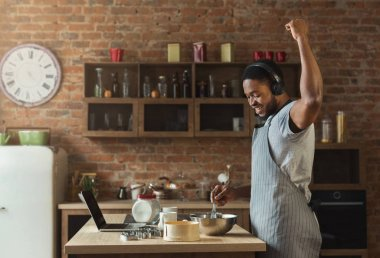 African american man listening to music and dancing in kitchen
