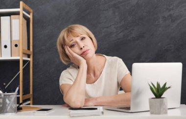 Bored mature businesswoman at office desk