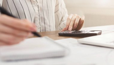 Woman with calculator counting and making notes