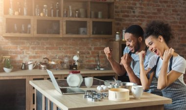 Happy black couple cooking pastry looking on laptop