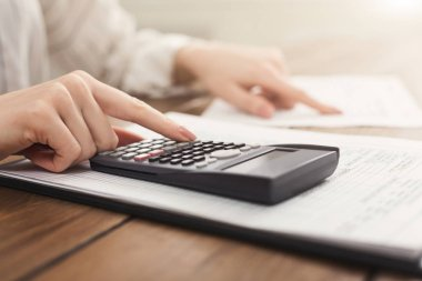 Woman hands with calculator and papers