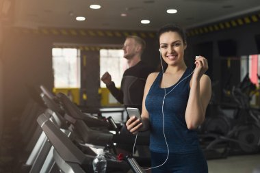 Attractive woman on treadmill in fitness club