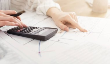 Female hands with calculator, sheet and graph