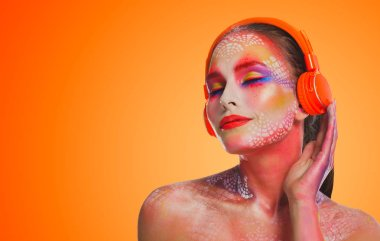 Bright beautiful woman in orange headphones