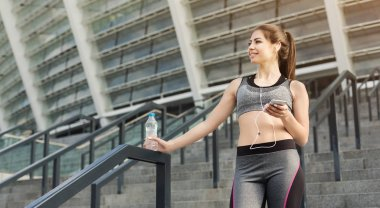 Sporty woman resting after running using smartphone