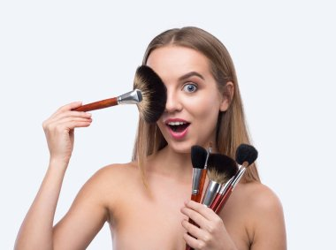 Happy woman with make up brushed isolated on white