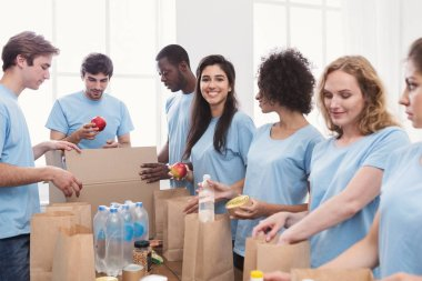 Volunteers packing food and drinks into paper bags