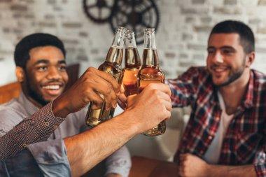 Friends clinking bottles of beer, celebrate meeting