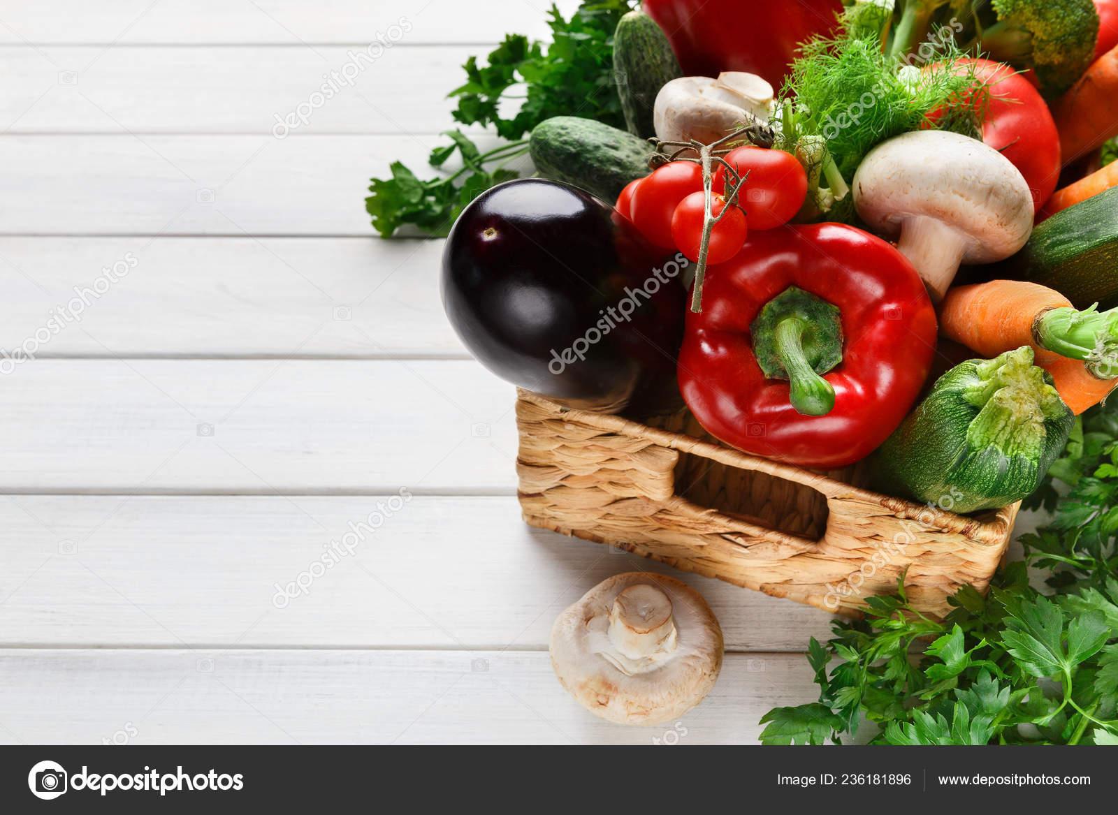 плетеная корзина с овощной ассортимент на деревянный стол