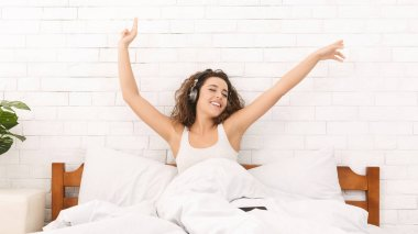 Excited woman listening to music on bed