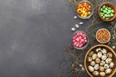 Easter holiday greeting background, with colorful candies and quail eggs