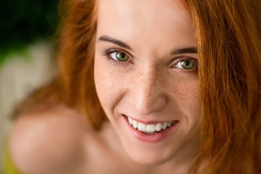 Cheerful redhead woman with freckles laughing at camera