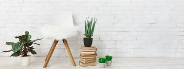 Indoor plants, chair with fur and stack of books at white brick wall background, copy space. Scandinavian comfort concept stock vector