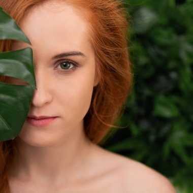 Attractive woman with natural red hair touching chin gently