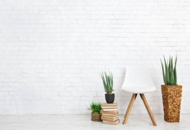 Indoor plants, scandinavian chair and stack of books on floor at white brick wall background, copy space stock vector