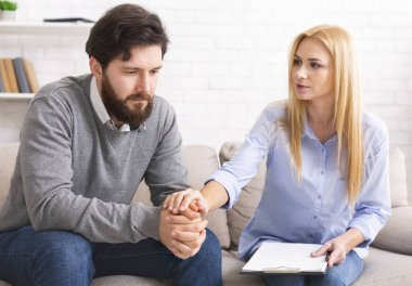 Female specialist supporting depressed patient at personal therapy in office