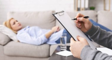 Psychologist listening to depressed patient and writing down notes