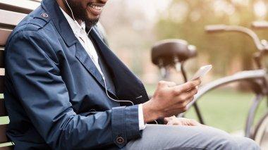 Man in earphones with smartphone having break outdoors