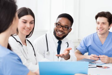 Multiracial medical team having meeting with doctor, discussing patients records stock vector