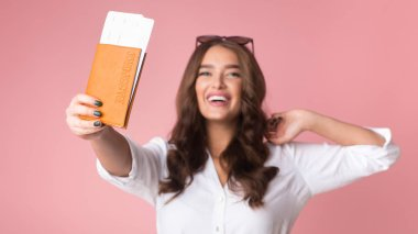 Cheerful girl traveller showing passport with tickets to camera
