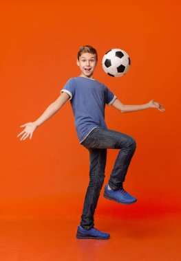Friendly emotional boy juggling with soccer ball