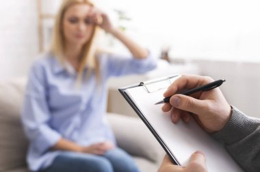 Depressed woman talking to psychotherapist, doctor taking notes