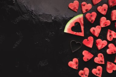Creative fruit serving. Heart shaped watermelon pieces, big slice and cutter on black background, copy space stock vector