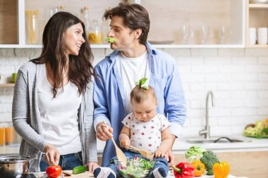 Young loving couple parents with their little baby son cooking in kitchen. stock vector